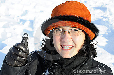Mature woman having fun in snow giving thumb up