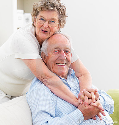 Mature woman hugging old man on couch