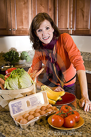 Mature woman in kitchen with fresh produce