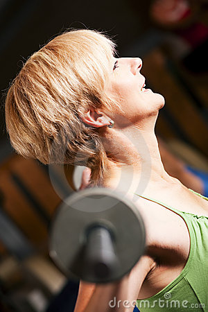 Mature woman lifting barbell
