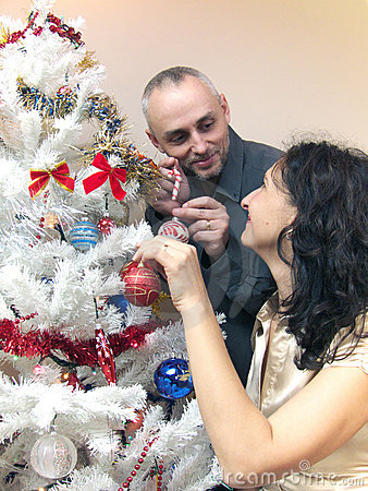 Woman and man decorating Christmas tree