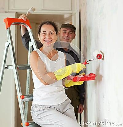 Mature woman and man making repairs