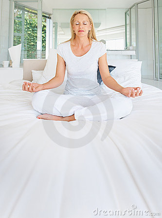 Mature woman meditating on bed in lotus position