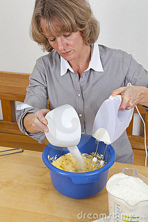 Mature woman mixing dough