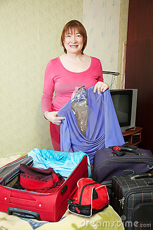 Mature woman packing suitcases