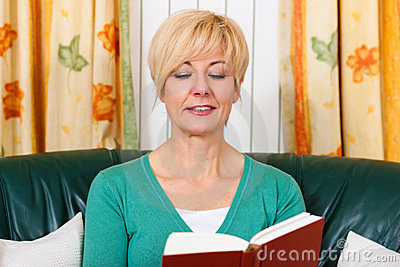 Mature woman is reading a book