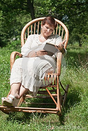 Mature woman reading book in rocking chair