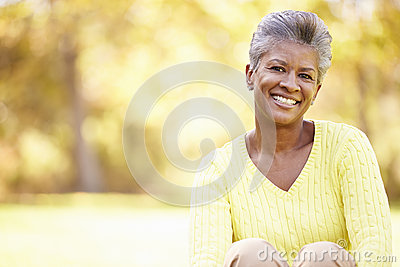 Mature Woman Relaxing In Autumn Landscape
