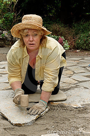 Mature woman setting pavers