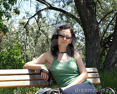 Mature woman sitting in city park