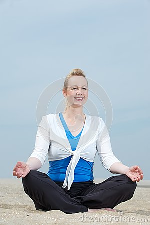 Mature woman sitting in yoga position at beach