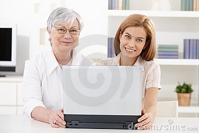 Mature woman and young daughter smiling happily