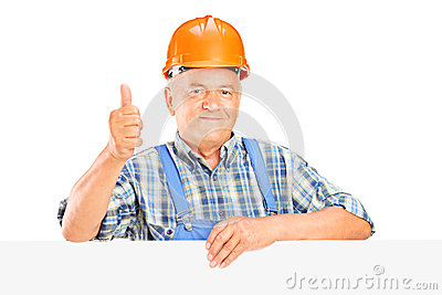 Mature worker with helmet posing behind a panel with thumb up