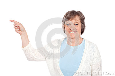 Matured casual lady pointing at copy space