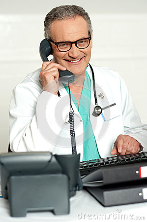 Matured physician communicating on phone