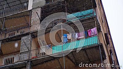 Mauvais district de la ville Vêtements accrochant sur une corde à linge dans un bâtiment pendant la pluie banque de vidéos