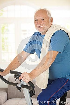 Mayor activo que usa la bici de ejercicio