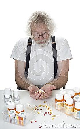 Mayor con porciones de prescripciones y un puñado de píldoras