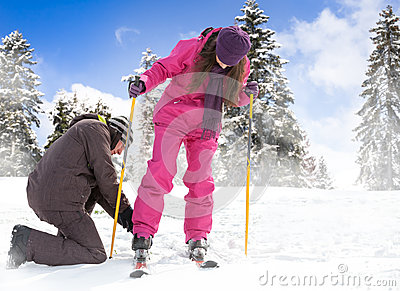 Mężczyzna pomaga jej dziewczyny stawiać jej narty