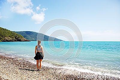 Mädchen auf dem korallenroten Strand, der heraus zum Meer schaut
