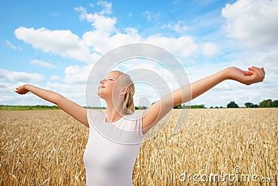 Mädchen, das auf einem Getreidegebiet mit ihren Armen angehoben steht