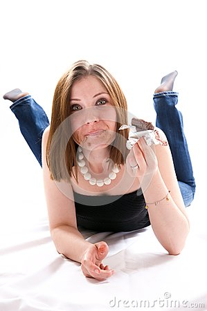 Mädchen, das auf Boden liegt und Schokolade isst