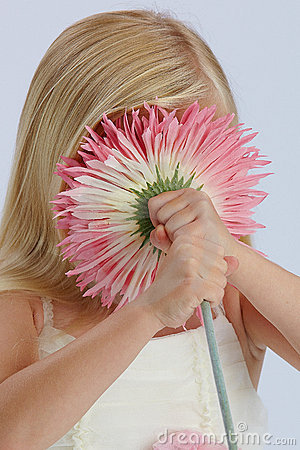 Mädchen, das hinter rosafarbener Blume sich versteckt