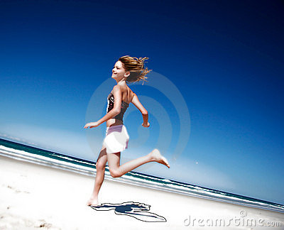Mädchen, das hinunter den Strand läuft