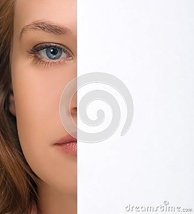Mädchen, das unter Blatt Papier sich versteckt