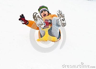 Mädchen hat Spaß, indem sie hinunter den schneebedeckten Hügel sledging