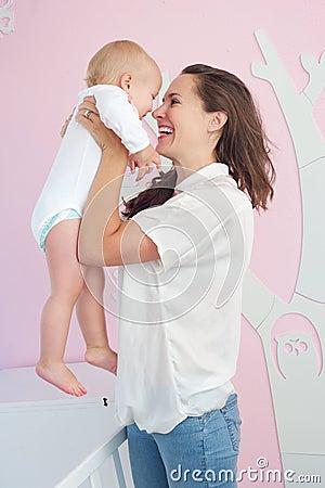 Mãe alegre que abraça o bebê bonito em casa
