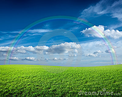 Meadow under blue sky and rainbow