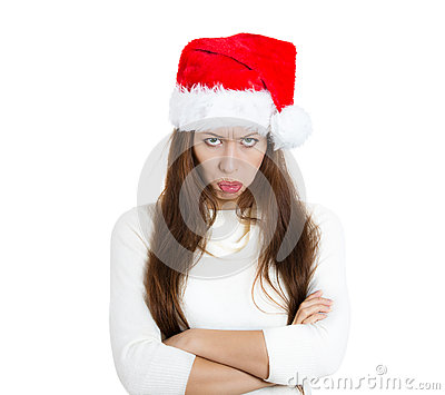 Mean, grumpy, unhappy, annoyed young woman, wife in red santa claus hat arms crossed folded looking at you