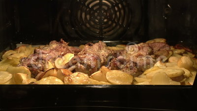 Meat dish in the oven. Time-laps. Meat and potatoes baked in the oven stock footage