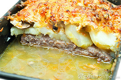 Meat topped with potatoes mushrooms
