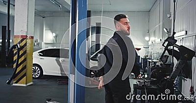 Mecánico de auto-operarios de servicio disfrutando del día en el trabajo mientras arregla el auto que baila y se mueve gracioso f metrajes