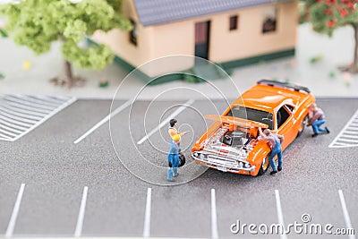 Mecánicos miniatura que trabajan en un coche