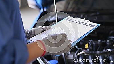 Mecânica automática lendo papel de formulário de declaração de seguro antes da manutenção e conserto do carro para o cliente na o video estoque
