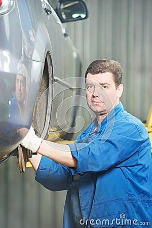 Mecânico que instala a roda de carro na estação do serviço