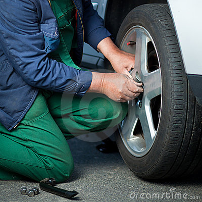 Mechanic changing a wheel of a modern car