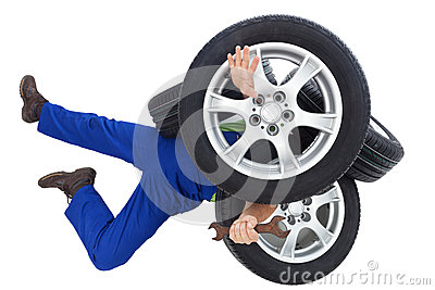 Mechanic covered by car tires
