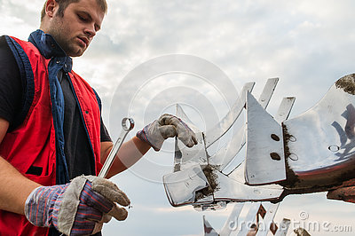 Mechanic fixing plow on the tractor Stock Photo