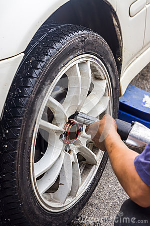 Mechanic hands with tool changing tyre of car