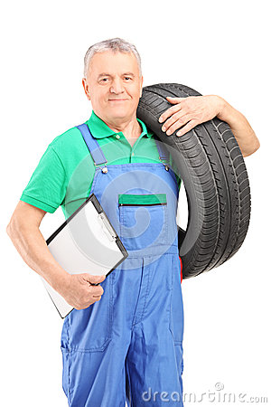 Mechanic holding a vehicle tire and a clipboard