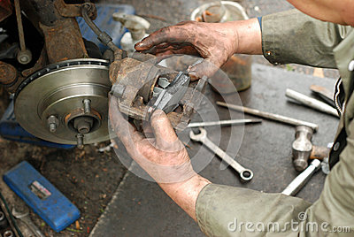 Mechanic pushing new brake pad into old caliper.