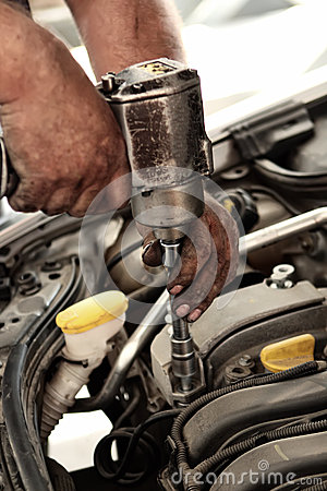 Mechanic using impact wrench for engine