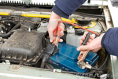 A mechanic using jumper cables