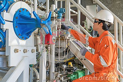 Mechanical engineering inspector check pressure of gas booster compressor engine before startup. Stock Photo