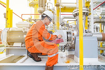 Mechanical technician checking and logging data and lube oil lubrication system of electric motor and centrifugal pump. Stock Photo