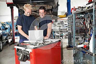 Mechanics with laptop in garage